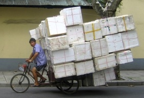 A man rides a bike laden with styrofoam containers down a street in Shanghai